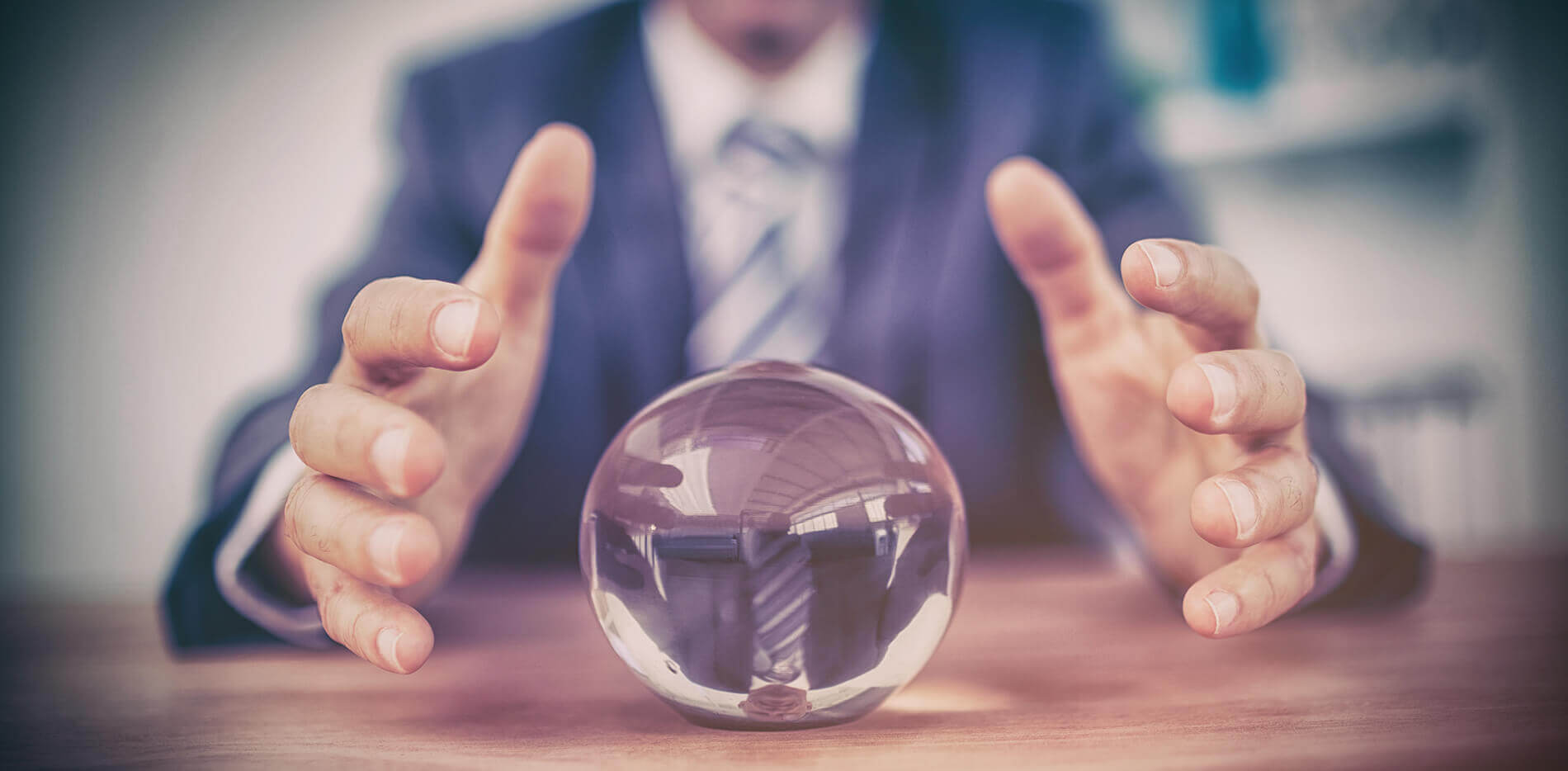 two hands covering a small crystal ball